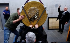 Workers use a crane to unload the world's largest gold coin which is on promotional display in Munich